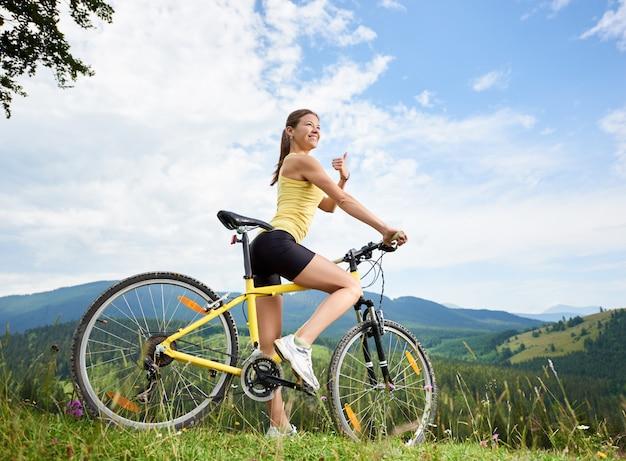 Aantrekkelijke gelukkig vrouwelijke wielrenner rijden op gele mountainbike op een met gras begroeide heuvel, duimen opdagen, genieten van zomerdag in de bergen. buitensportactiviteit, levensstijlconcept