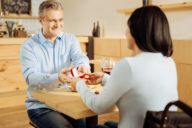 Aantrekkelijke, gelukkige blonde man die lacht en zijn geliefde donkerharige gehandicapte vrouw voorstelt en een ring vasthoudt tijdens een romantisch diner