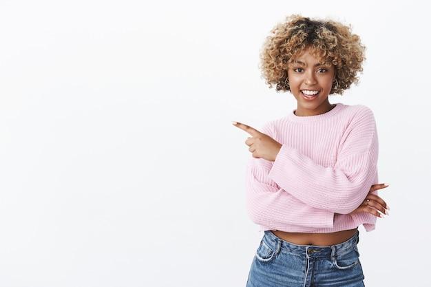 Aantrekkelijke gelukkige en enthousiaste afro-amerikaanse vriendin met blond krullend kapsel wijzend naar de linkerbovenhoek en glimlachend opgewonden en gedurfd, flirterig en koket over de witte muur
