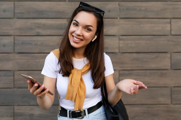 Aantrekkelijke gelukkige glimlachende jonge vrouw die vrijetijdskleding draagt die zich in de straatholding bevindt en gebruikt