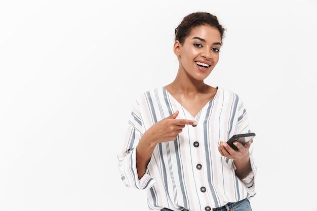 Aantrekkelijke gelukkige jonge afrikaanse vrouw die vrijetijdskleding draagt die geïsoleerd over een witte muur staat, mobiele telefoon gebruikt, viert