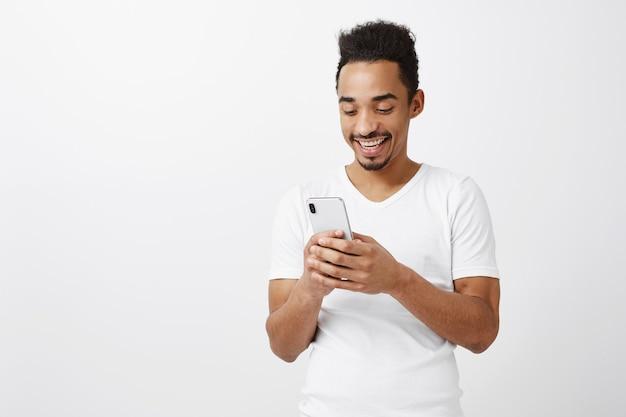 Aantrekkelijke gelukkige jonge afro-amerikaanse man met behulp van mobiele telefoon en lachend op scherm, chatten, met behulp van applicatie