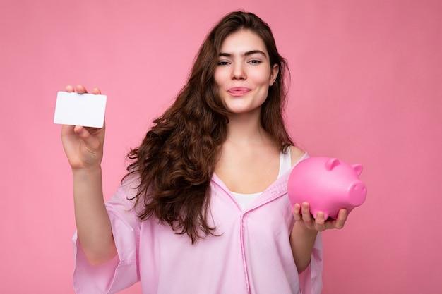 Aantrekkelijke gelukkige jonge brunette vrouw dragen shirt geïsoleerd op roze achtergrond met lege ruimte en