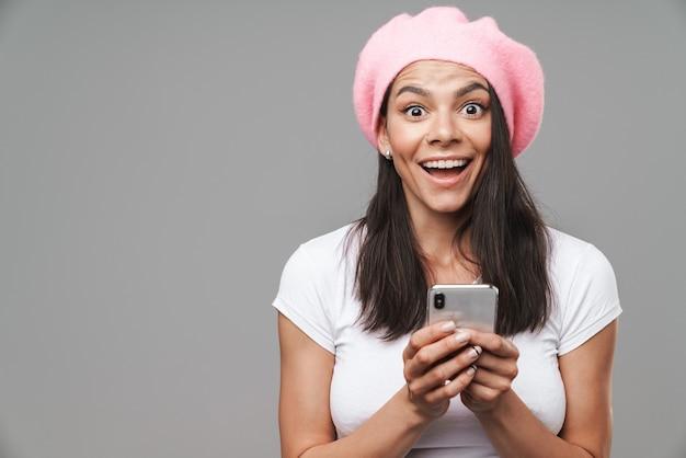Aantrekkelijke gelukkige jonge donkerbruine vrouw die baret draagt die zich geïsoleerd over grijze muur bevindt, mobiele telefoon houdt, succes viert