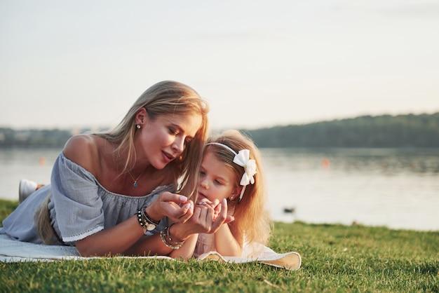 Aantrekkelijke gelukkige jonge moeder die met haar leuke dochter op het gras in het park ligt.