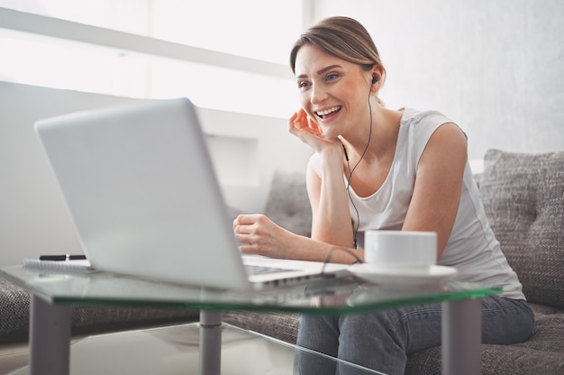 Aantrekkelijke gelukkige jonge student online studeren thuis, met behulp van laptopcomputer, hoofdtelefoons, met video-chat, zwaaien. werken op afstand, onderwijs op afstand. videoconferentie of virtueel evenement in quarantaine