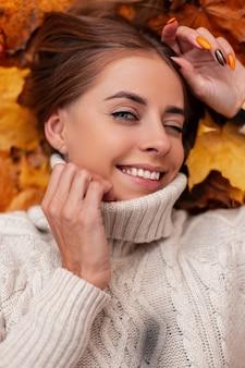 Aantrekkelijke gelukkige jonge vrouw knipoogt kijkend naar de camera. portret van een vrolijk positief meisje in een gebreide witte trui in de herfst oranje gebladerte in het park. uitzicht van boven.