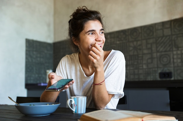 Aantrekkelijke gelukkige jonge vrouw met gezond ontbijt in de keuken thuis, berichten op mobiele telefoon