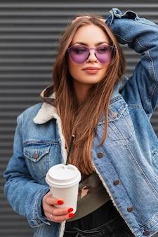Aantrekkelijke gelukkige jonge vrouw model in trendy paarse bril in stijlvol denim jasje met kopje warme drank poseren in de buurt van een metalen wand buiten. het mooie hipstermeisje met koffie geniet van de lentedag.