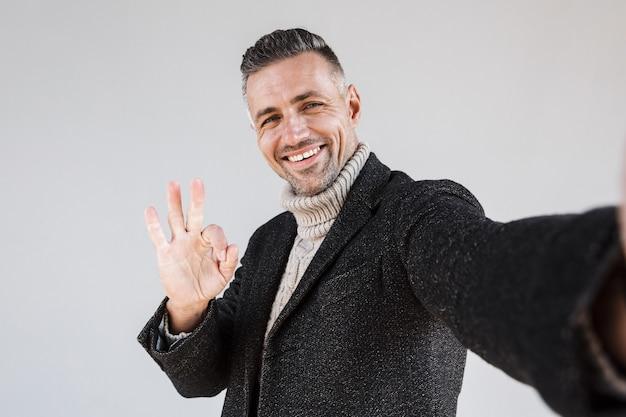 Aantrekkelijke gelukkige man met een jas die geïsoleerd staat over een grijze muur, een selfie neemt, ok toont