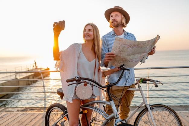 Aantrekkelijke gelukkige paar reizen in de zomer op de fiets, man en vrouw met blond haar boho hipster stijl mode samen plezier, op zoek in kaart sightseeing fotograferen op camera