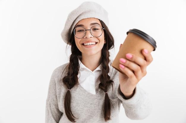 Aantrekkelijke gelukkige schoolvrouw die unifrom draagt dat over een witte muur staat, met afhaalmaaltijden koffiekopje