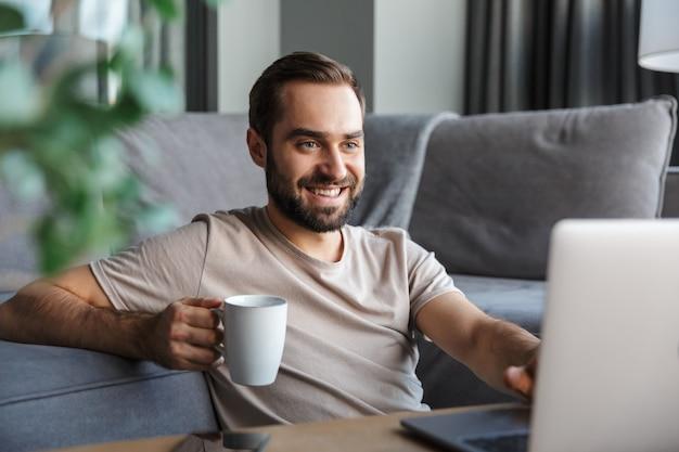 Aantrekkelijke gelukkige slimme jonge man zittend op een vloer in de woonkamer, bezig met; laptopcomputer, koffie drinken