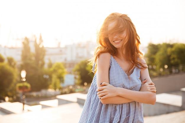 Aantrekkelijke gelukkige vrouw die zich met gevouwen wapens bevindt