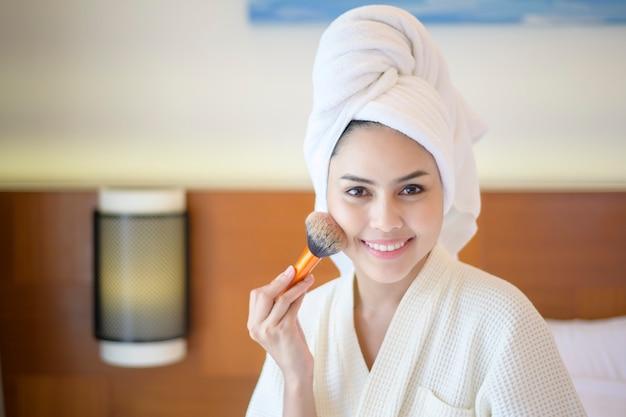 Aantrekkelijke gelukkige vrouw in witte badjas past natuurlijke make-up met cosmetische poederborstel, beauty concept toe.