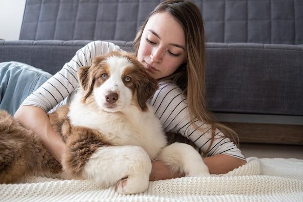 Aantrekkelijke gelukkige vrouw knuffel kleine schattige australische herder rode drie kleuren puppy hondje.