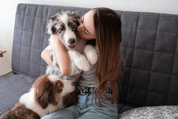 Aantrekkelijke gelukkige vrouw kus kleine schattige australische herder blauwe merle puppy hondje. huisdieren zorg concept. liefde en vriendschap