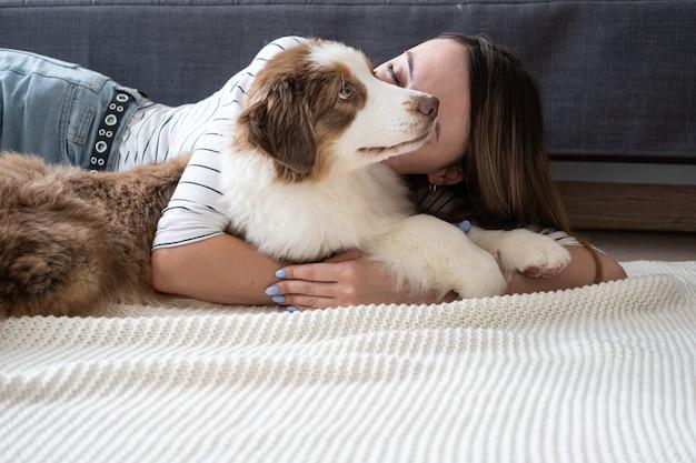 Aantrekkelijke gelukkige vrouw kus kleine schattige australische herder rode drie kleuren puppy hondje.
