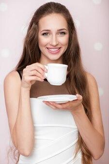 Aantrekkelijke gelukkige vrouw met witte kop met koffie op roze achtergrond