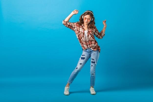 Aantrekkelijke gelukkige vrouw poseren in vrolijke bui luisteren naar muziek in koptelefoon in geruit overhemd en spijkerbroek geïsoleerd op blauwe studio achtergrond, opzoeken