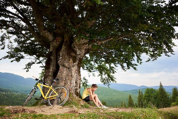 Aantrekkelijke gelukkige vrouw wielrenner zitten in de buurt van gele berg fiets onder grote boom, genieten van zomerdag in de bergen. buitensportactiviteit, levensstijlconcept