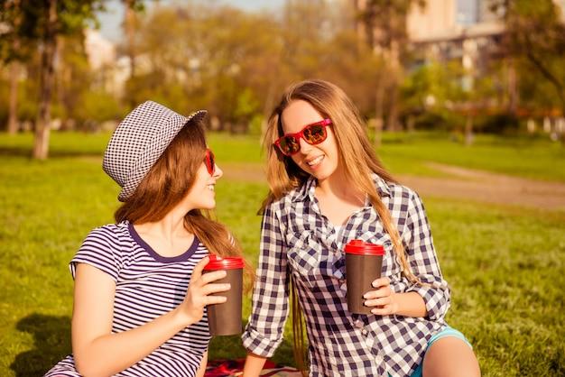 Aantrekkelijke gelukkige vrouwen in glazen die picknick hebben en koffie drinken