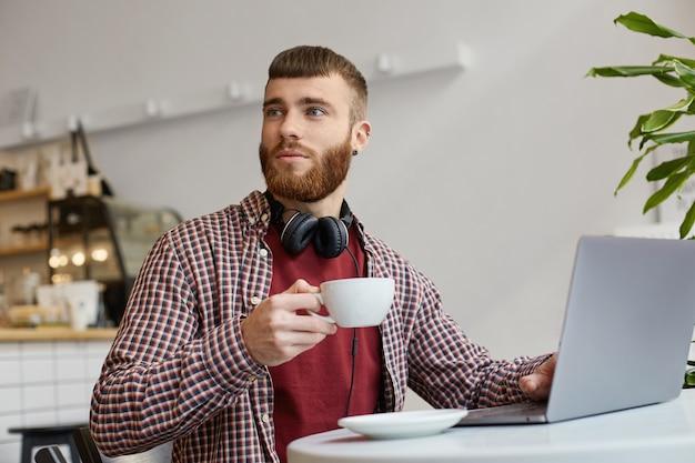 Aantrekkelijke gember bebaarde man aan het werk op een laptop zittend in een café, koffie drinkend, gekleed in basiskleding, wegkijkend, het lijkt erop dat hij een oude vriend ziet.