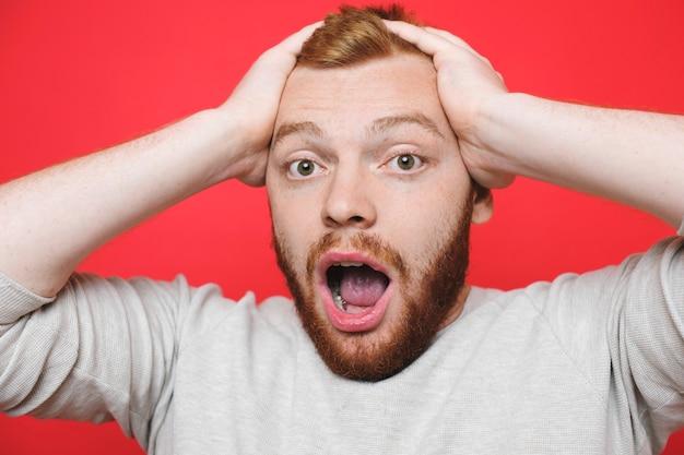 Aantrekkelijke gember man houden handen op het hoofd en kijken naar camera met geschokte gezichtsuitdrukking terwijl hij op heldere rode achtergrond staat