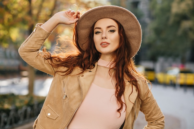 Aantrekkelijke gember vrouw met lang kapsel poseren in beige jas op straat muur vervagen