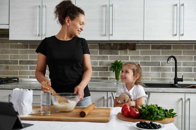 Aantrekkelijke gemengd ras vrouw, kijkend naar haar schattige babymeisje tijdens het kneden van deeg. moeder en dochter koken samen in de keuken