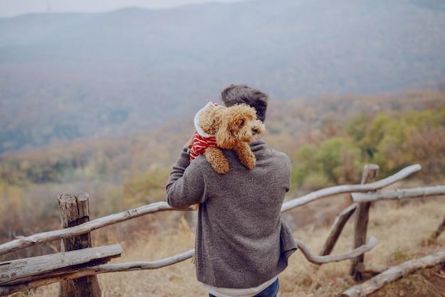 Aantrekkelijke gemengde rasmens die zijn houdende van hond houdt terwijl status in aard bij daling.
