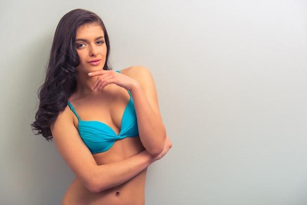 Aantrekkelijke gepassioneerde jonge vrouw in blauw ondergoed.