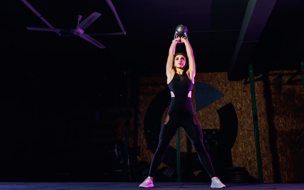 Aantrekkelijke geschikte vrouwenatleet die een schommeling van de ketelklok in gymnastiek uitvoeren
