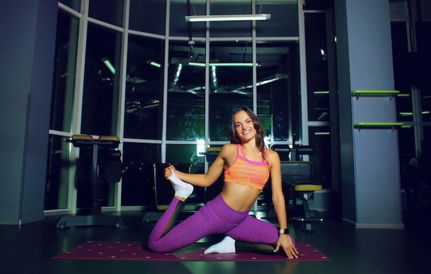 Aantrekkelijke geschiktheidsvrouwen die uitrekkende oefening uitvoeren. yoga concept.
