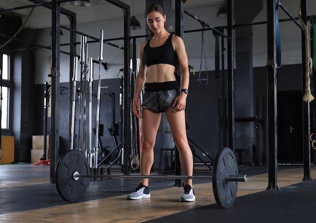 Aantrekkelijke gespierde geschikte vrouw die bouwspieren uitoefent.