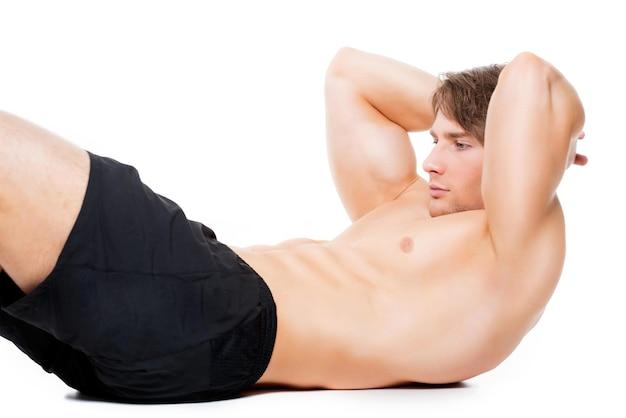 Aantrekkelijke gespierde sportman oefenen op een vloer - geïsoleerd op wit.