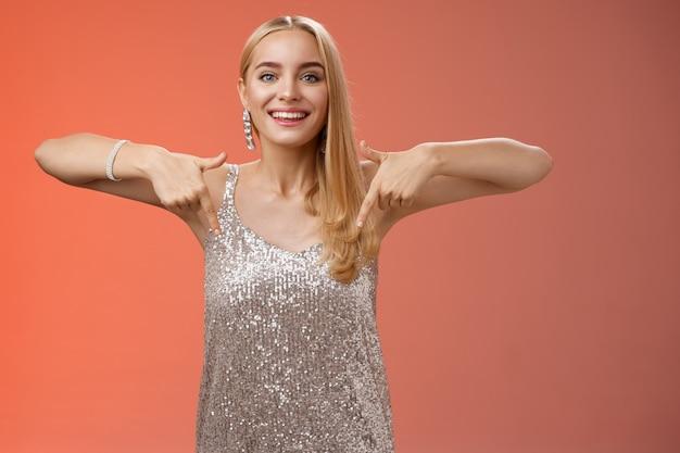 Aantrekkelijke glamour blonde vrouw in zilveren glinsterende jurk naar beneden glimlachend opgewonden
