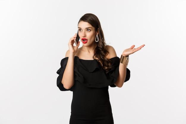 Aantrekkelijke glamourvrouw in zwarte jurk die op mobiele telefoon praat, een gesprek voert en er verrast uitziet, staande op een witte achtergrond.