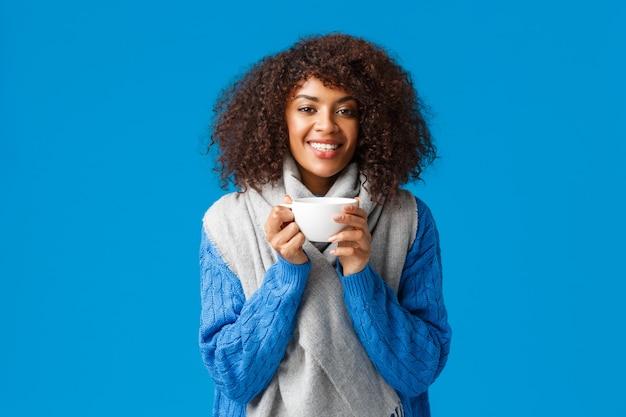 Aantrekkelijke glimlachende afro-amerikaanse gelukkige vrouw met krullend haar, wikkel zichzelf met sjaal en koffie drinken, blauwe muur.