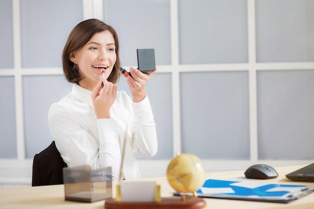 Aantrekkelijke glimlachende bedrijfsvrouw die make-up op kantoor doet
