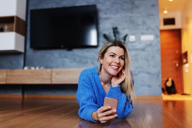 Aantrekkelijke glimlachende blonde jonge vrouw die op buik in de woonkamer ligt en slimme telefoon gebruikt om op sociale mediasites te hangen