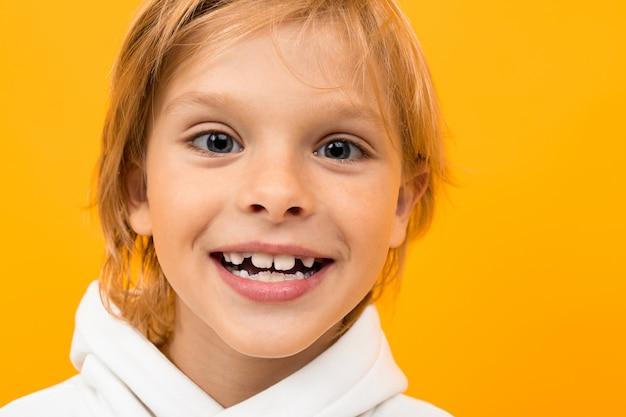 Aantrekkelijke glimlachende blonde jongen in een witte hoodie op een geel close-up