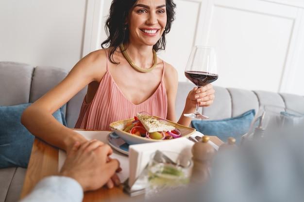 Aantrekkelijke glimlachende dame die aan tafel zit met eten en een glas wijn vasthoudt terwijl een heer haar hand vasthoudt