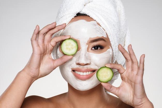 Aantrekkelijke glimlachende dame met scrab op de komkommerplakken van de gezichtsholding
