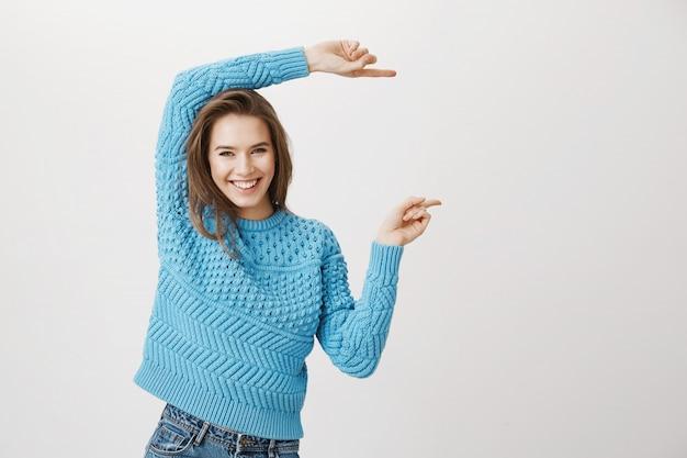 Aantrekkelijke glimlachende, gelukkige vrouw wijzende vingers rechts
