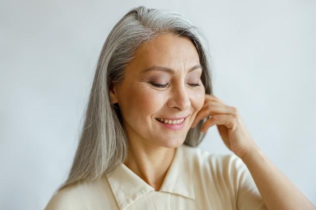 Aantrekkelijke glimlachende grijsharige dame in een stijlvol shirt raakt de wang met de hand aan op een lichte achtergrond in de studio. volwassen schoonheid levensstijl