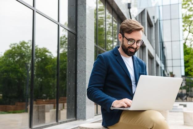 Aantrekkelijke glimlachende jonge, bebaarde man met een jas die aan een laptop werkt terwijl hij buiten in de stad zit