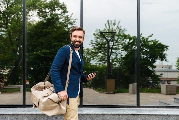 Aantrekkelijke glimlachende jonge bebaarde man met een jas die buiten op straat loopt, een tas draagt, een mobiele telefoon vasthoudt