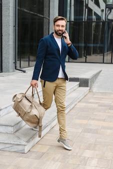 Aantrekkelijke glimlachende jonge, bebaarde man met een jas die buiten op straat loopt, een tas draagt, praat op een mobiele telefoon