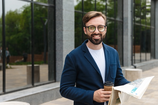 Aantrekkelijke glimlachende jonge bebaarde man met een jas die de krant leest terwijl hij buiten in de stad staat en afhaalkoffie drinkt